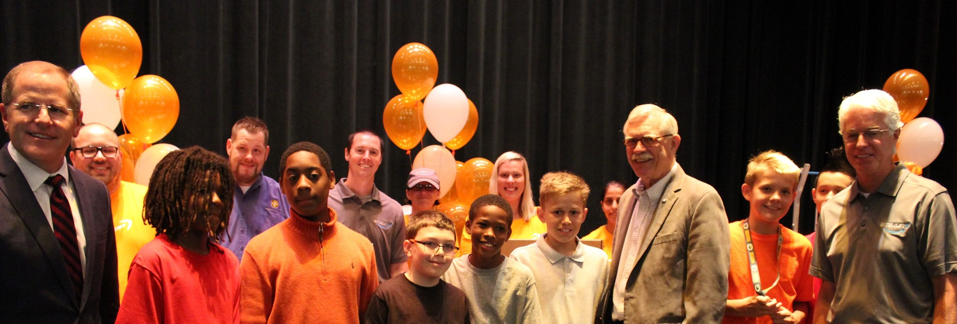 Students pose with Mayor Joe Meyer and Amazon representatives after large donation from Amazon.