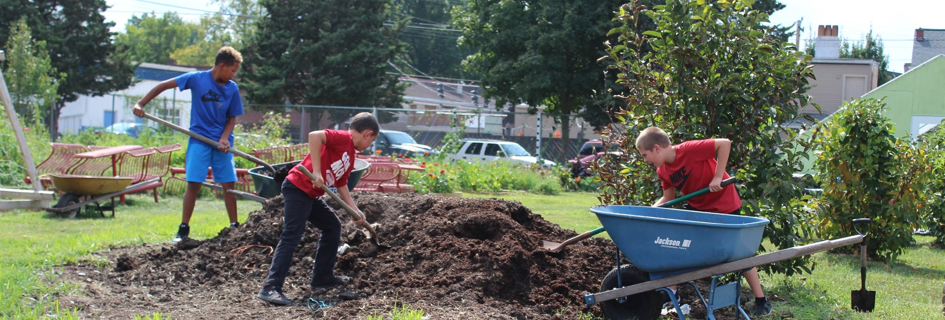 Students in the garden club, work on moving a pile of dirt.