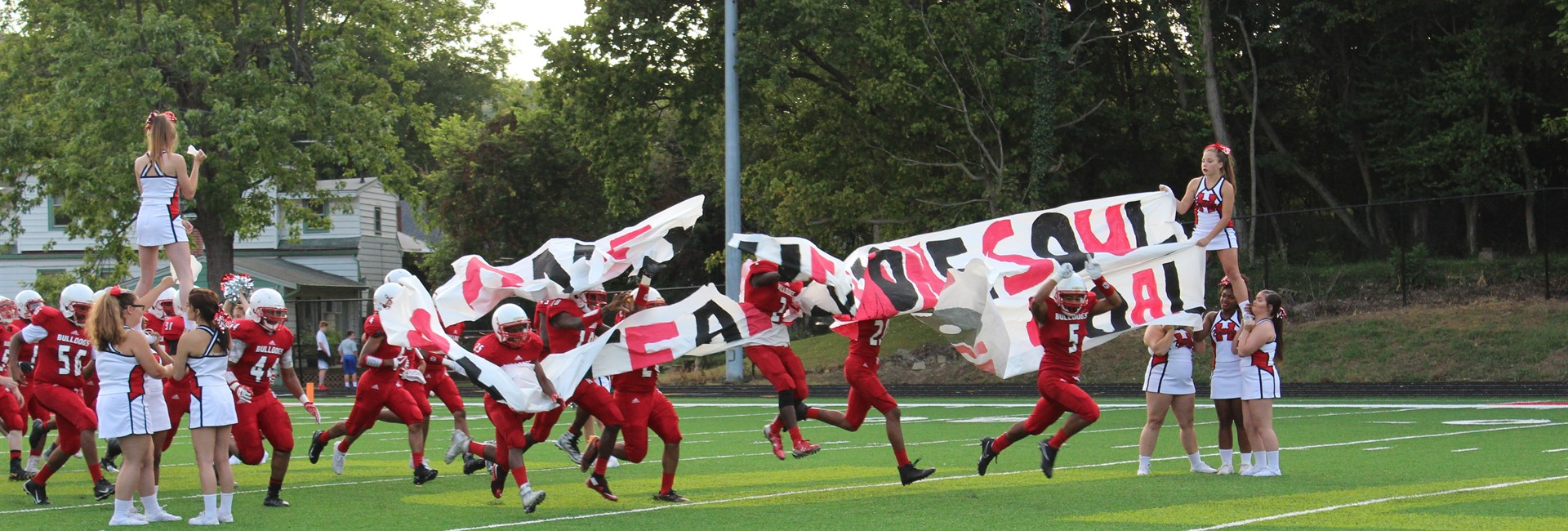 The Bulldog football team crashes through the banner to enter the field.